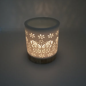 Ceramic white wax melt burner with ceramic wood effect base pictured in semi dark natural light with Butterfly apertures illuminated by the tealight within. (Tealight not included)