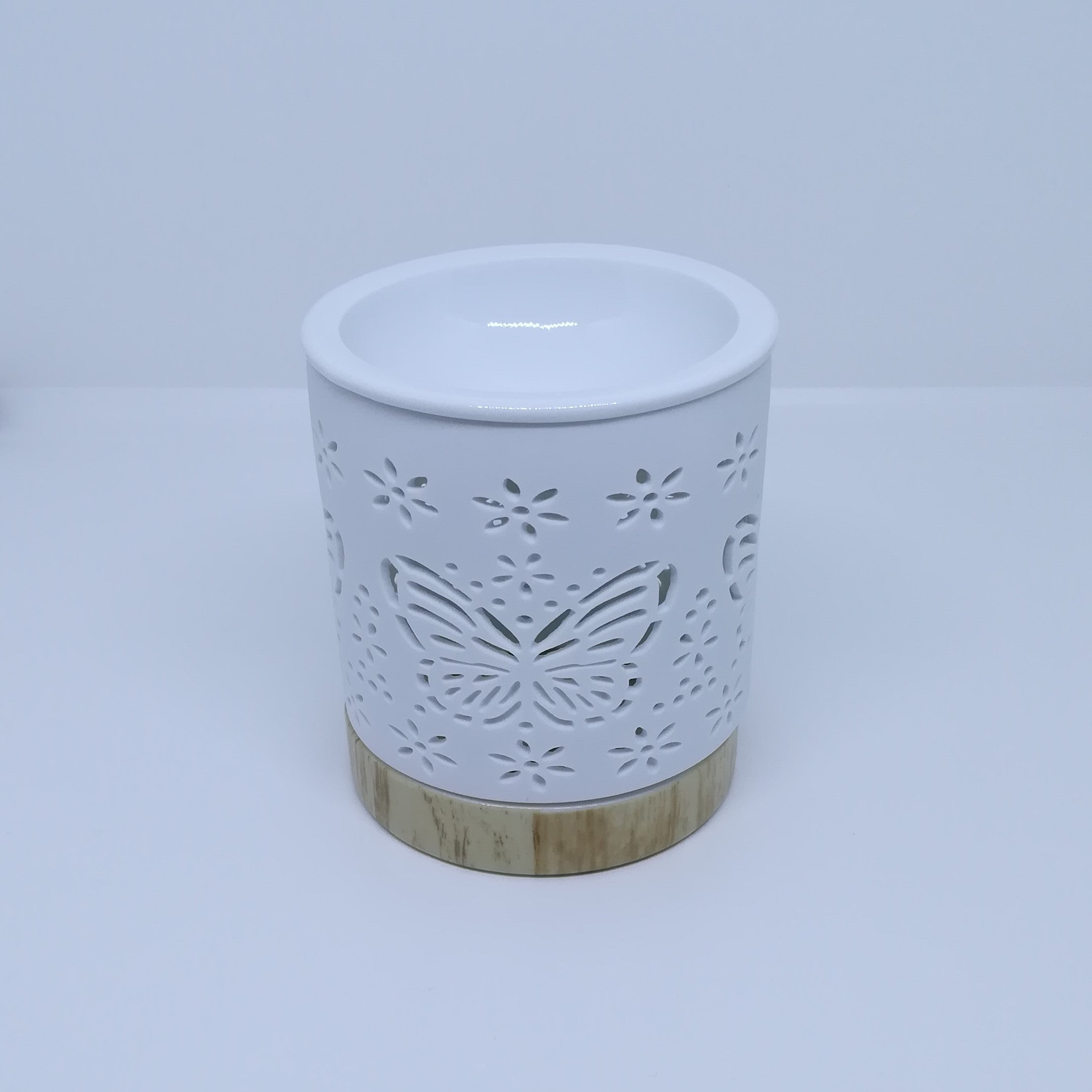 Ceramic white wax melt burner with ceramic wood effect base pictured under natural light.