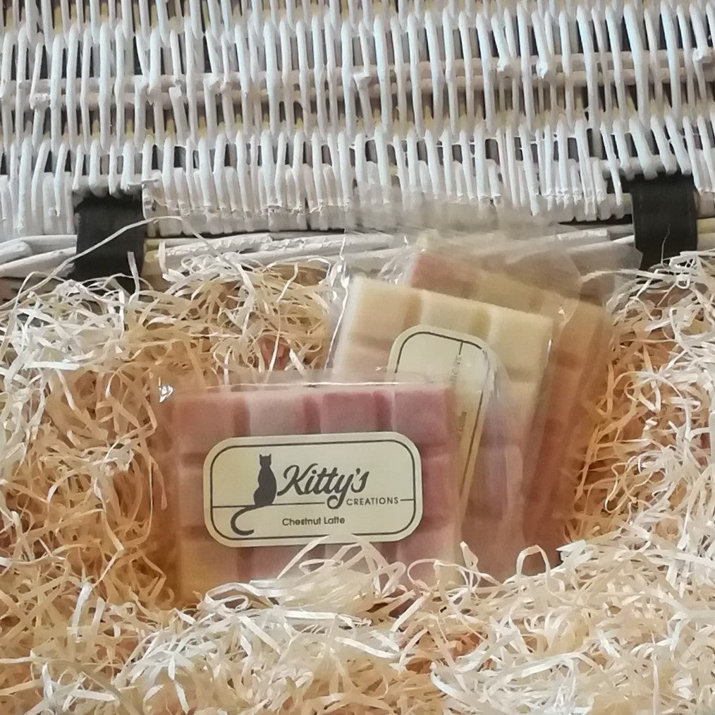 Three hand-made rectangular Wax Melts. Each is coloured a delicate rich brown blending to a light creamy yellow, resting in a basket of straw. Imagine yourself beside the fire as the horse chestnuts roast.