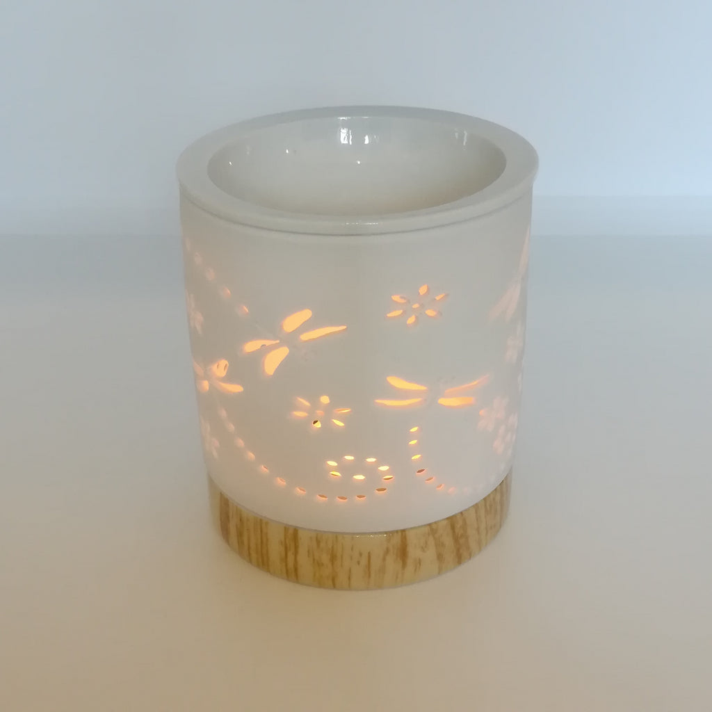 Ceramic white wax melt burner with ceramic wood effect base pictured under natural light with dragonfly apertures illuminated by the tealight within. (Tealight not included).