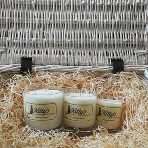Three white candles, one large, one medium and one small are pictured in a basket of straw. Hand poured with soy wax, in elegant glass tumblers and available in three different sizes, these candles are the perfect gift. Each reveals a scent evoking warm sunshine, a tropical shore with pristine white sands, a perfect holiday.