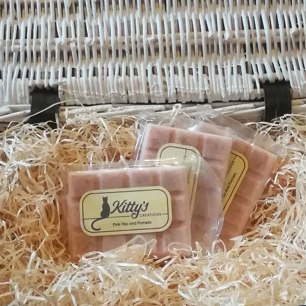 Three hand-made rectangular Wax Melts. Each is coloured a delicate pink and resting in a basket of straw. This is fragrance lets you smell the celebrations as the bubbles fizz and the celebrations begin