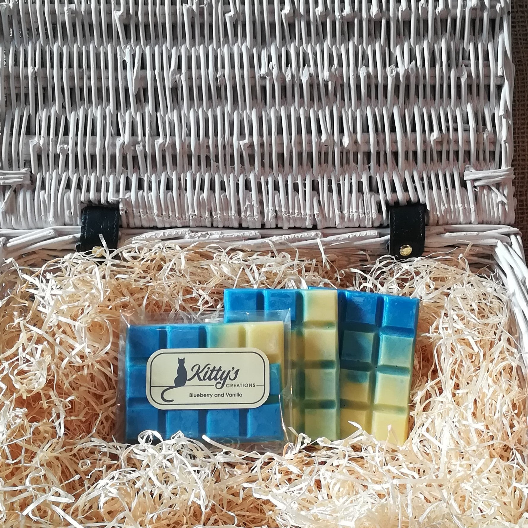 Three hand-made rectangular Wax Melts. Each is blended from dark blue to pale yellow, coloured to show the succulent balance of aromas within. Each melt is resting in a basket of straw and scented to stimulate your taste buds.