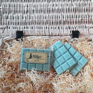 Three hand-made rectangular Wax Melts all Duck Egg Blue, resting in a basket of straw. Each melt bursting with the childhood feeling of playing hide-and-seek in between the laundry sheets blowing in the spring breeze.