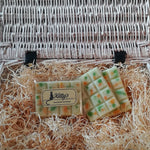 Three hand-made rectangular Wax Melts. Each is a light delicate green, overlaid with orange and forest green speckles and spots they are resting in a basket of straw. Each melt bursting with the mild and delicate fragrance of Lemongrass matched with the zesty freshness of ginger, combined to awaken your senses.