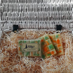 Three hand-made rectangular Wax Melts. Each is a light delicate green, overlaid with orange and fresh green speckles and spots they are resting in a basket of straw. Each melt containing mandarin and lime blend perfectly together before you sense the warmth of peppery basil and undertones of amberwood and caraway seeds taking you away on a tropical dream.