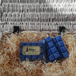 Three hand-made rectangular Wax Melts, each one midnight blue with a soft dusty surface and delicate Jasmine flowers beneath, resting in a basket of straw. Each melt reveals a delicate soothing Jasmine scent.