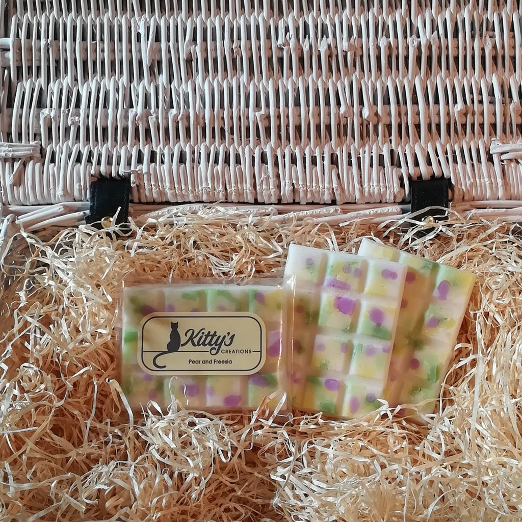 Three hand-made rectangular Wax Melts. Each is a natural wax cream colour, overlaid with fresh pear green, light yellow and purple speckles and resting in a basket of straw. Each melt bursting with the delicious aroma of fruity Pear entwining with the freshness of Freesia, combining to awaken and invigorate your senses.