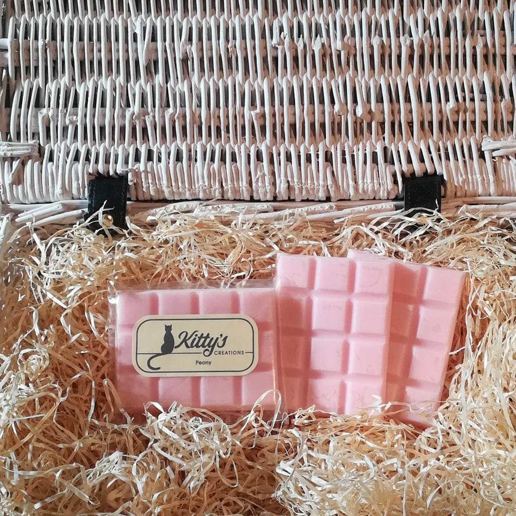 Three hand-made rectangular Wax Melts. Each is a delicate pastel pink resting in a basket of straw. Each melt effortlessly releases the light subtle aroma of Peony allowing the cool freshness of a late Spring morning to drift around your home.