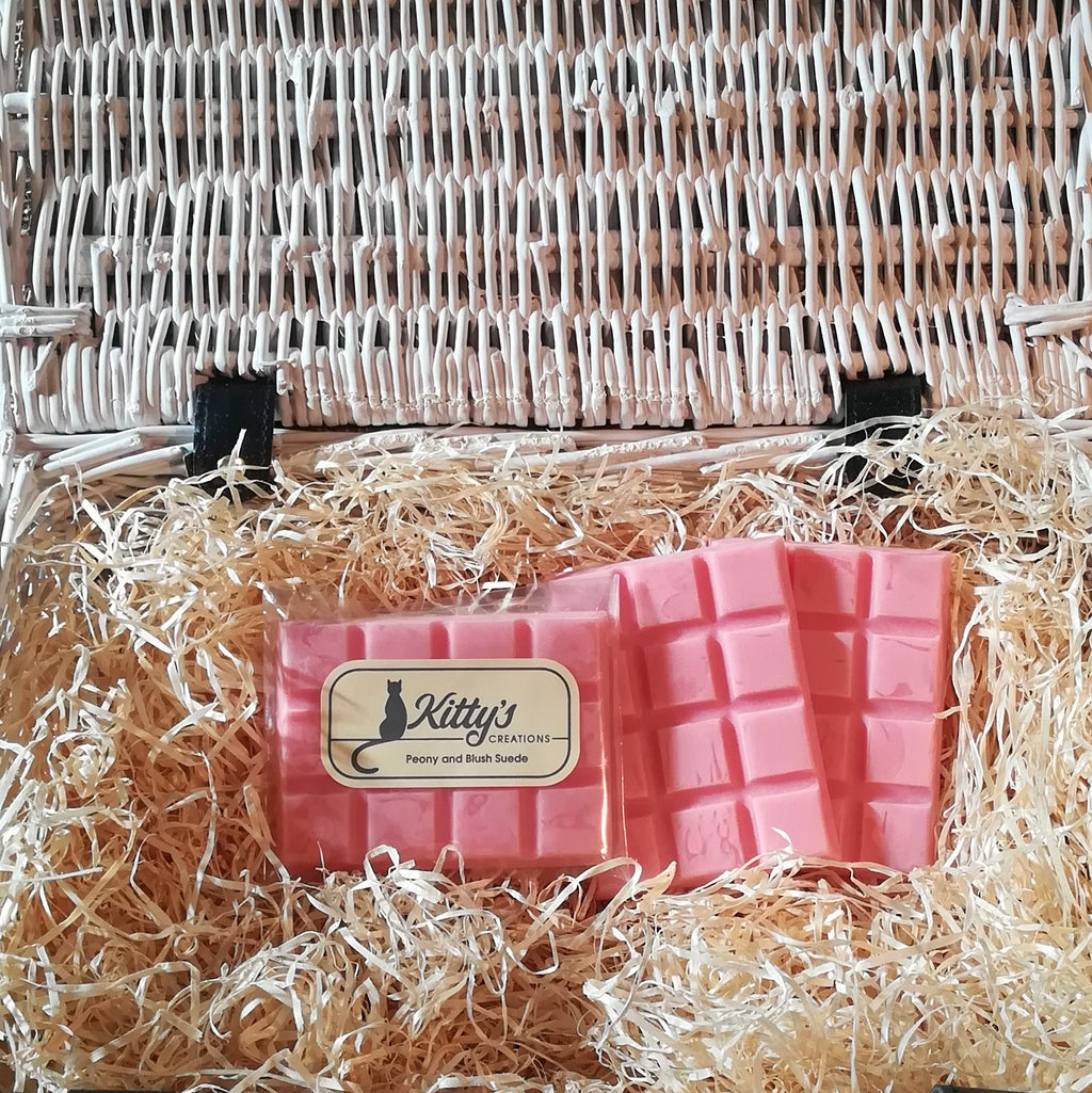 Three hand-made rectangular Wax Melts. Each is Geraldine pink resting in a basket of straw. Each melt effortlessly releases the subtle aroma of Peony mingled with the woody richness of Suede, filling your home with the essence of summer.
