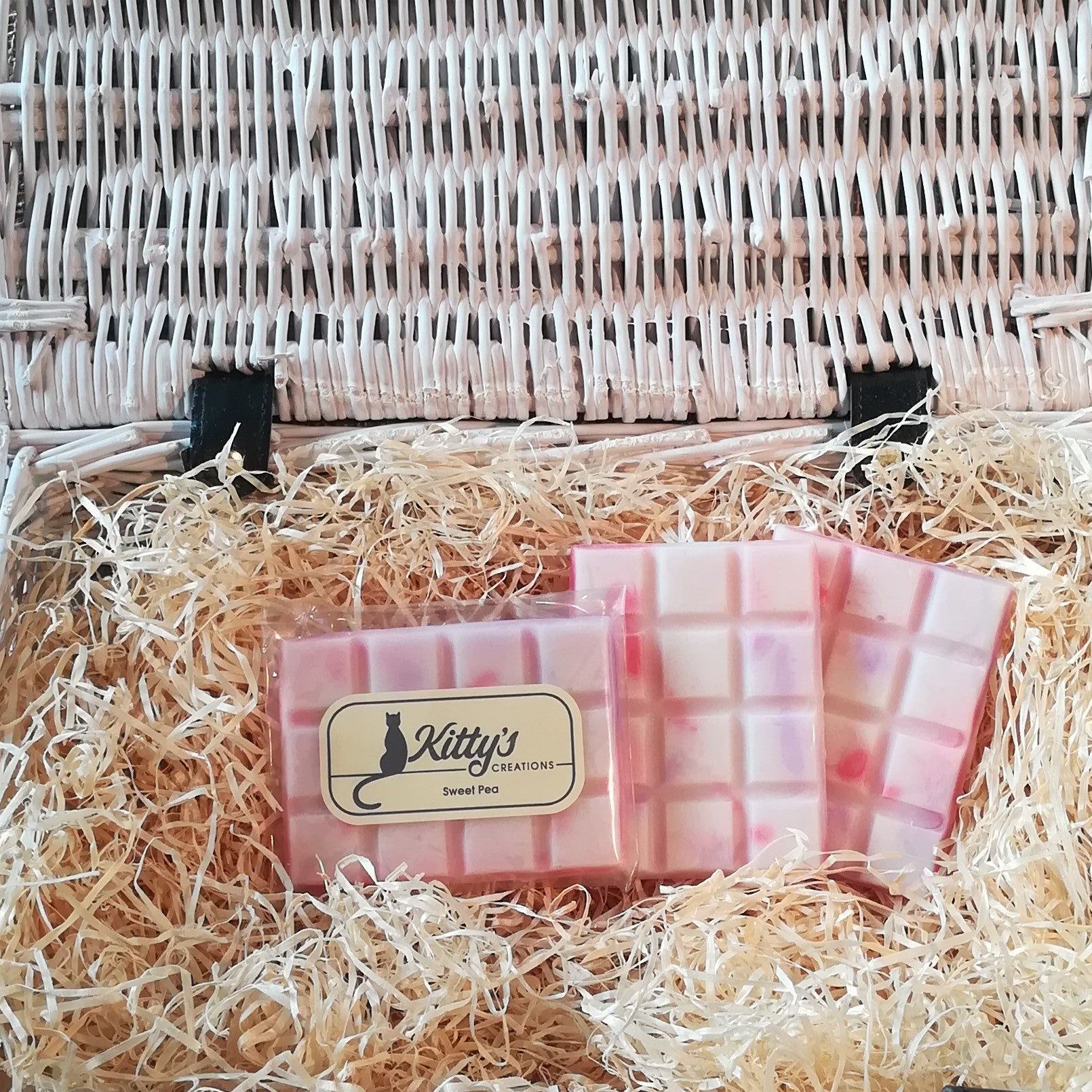 Three hand-made rectangular Wax Melts. Each is white Soy wax, coloured with gentle Sweet Pea marbling patterned in their delicate pink and purple shades, the melts are resting in a basket of straw. Each melt is alive with Sweet Peas, giving you the uplifting fragrance of walking through flowering archways and pergolas.