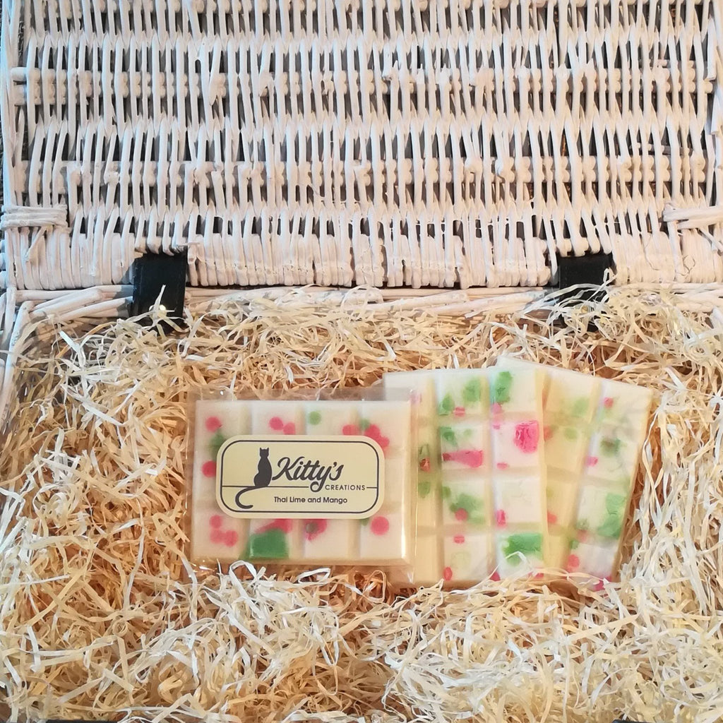 Three hand-made rectangular Wax Melts. Each is white Soy wax, coloured with a pattern of Mango red and Thai Lime green dots randomly arranged, the melts are resting in a basket of straw. Each melt is a vibrant mix of aromas, taking you back to those warm humid days and the sounds of night-time crickets on the trip you will never forget.