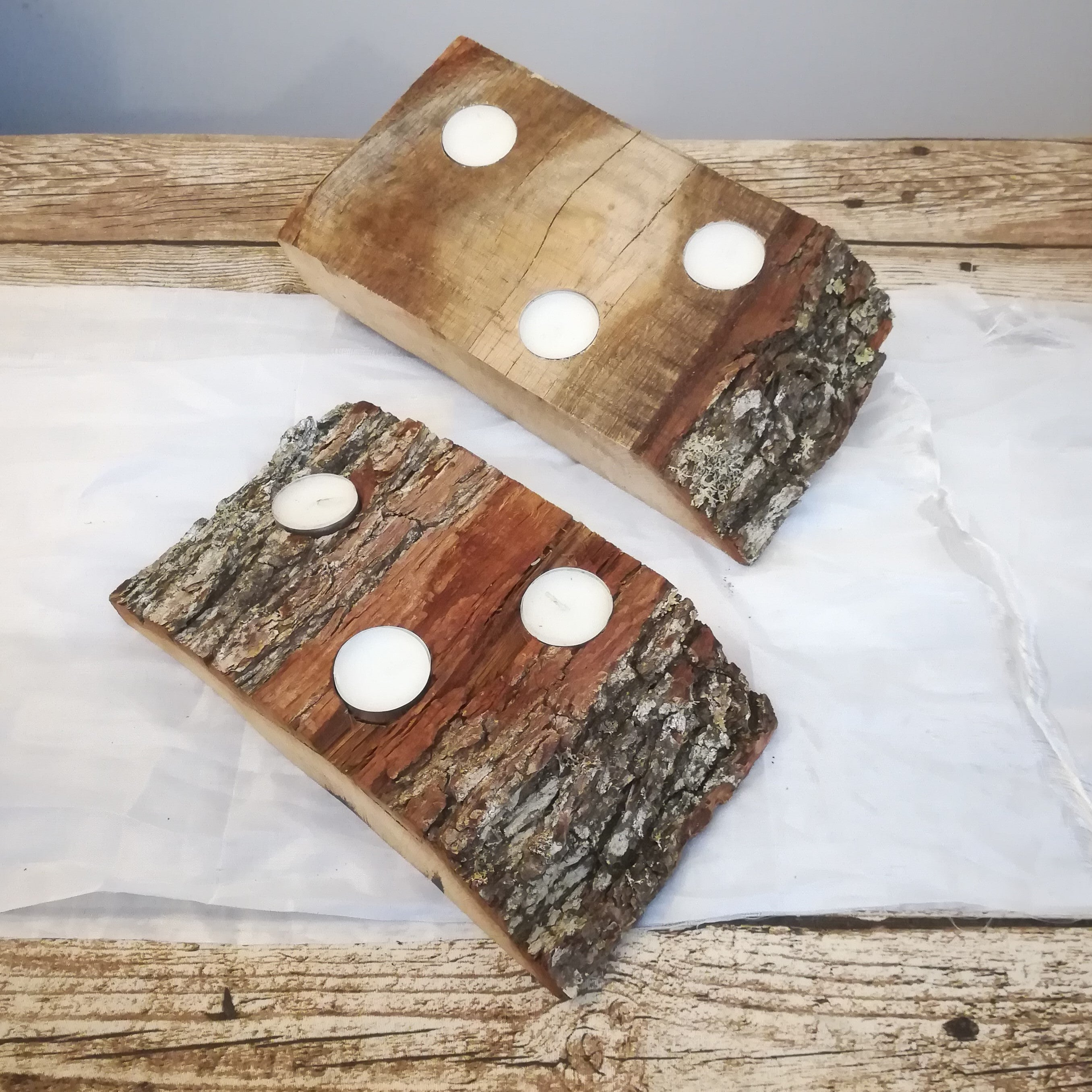 Two oak tea light, tea-light holders on wooden table, also ideal for patio or garden.