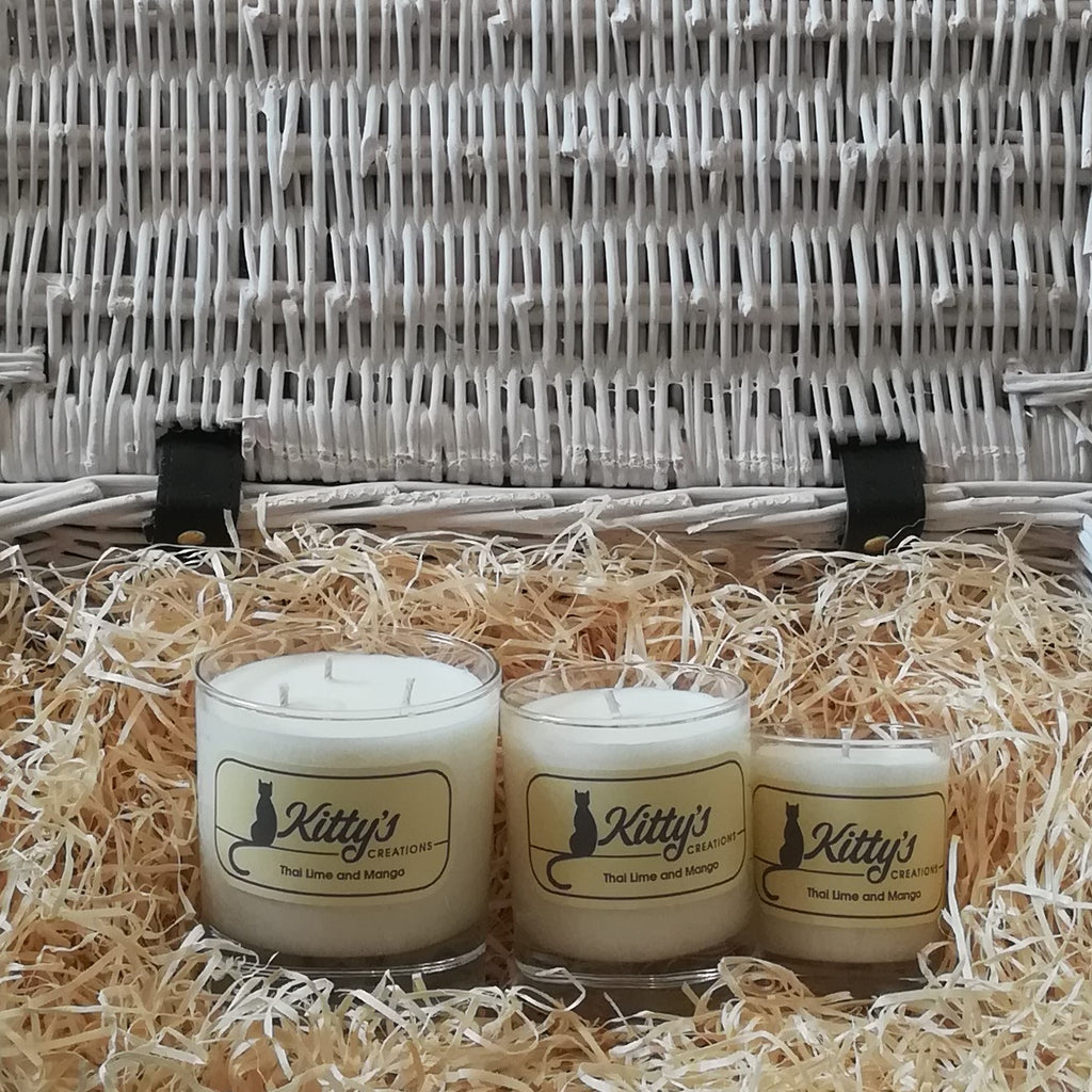 Three glass tumblers, one large, one medium, and one smaller are filled with soy wax, pictured in a basket of straw. These candles are the perfect gift. Each reveals a scent which is a vibrant mix of aromas, taking you back to those warm humid days and the sounds of night-time crickets on the trip you will never forget.