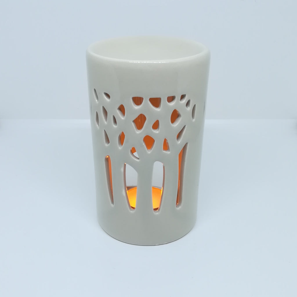A ceramic wax melter featuring a wintertime woodland apature with tree limbs reaching upwards illuminated by the tea-light within. (Tea light not included).