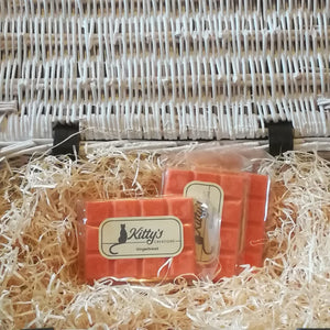 Three hand-made rectangular Wax Melts. Each is coloured a vibrant orange, and resting in a basket of straw. Imagine the smell of fresh gingerbread emerging from the oven, waiting for it to cool while you warm yourself in the kitchen.
