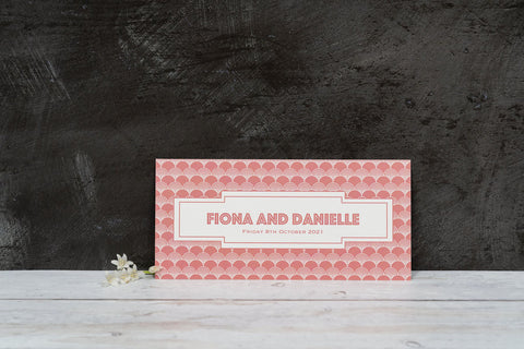 Image copyright EKR Studio. Bookmark-style wedding invitation, with a Gatsby-style pattern and blush background. View of the back, with the couple's names and the date of their wedding.