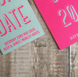 Close-up of the textured card. Bookmark-style wedding invitation/save the date. The overall style is typographic and bold.