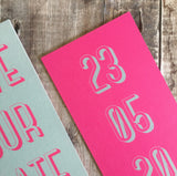 Close-up of the textured card. Bookmark-style wedding invitation/save the date. Back view. This has a pink fluorescent background, with the date of the wedding in a teal colour. The overall style is typographic and bold.