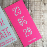 Bookmark-style wedding invitation/save the date. Back view. This has a pink fluorescent background, with the date of the wedding in a teal colour. The overall style is typographic and bold.