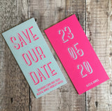 Bookmark-style wedding invitation/save the date. Front and back view. Front (left) has a teal blue background, with fluorescent pink text. Back (right) has a pink fluorescent background, with the date of the wedding in a teal colour. The overall style is typographic and bold.