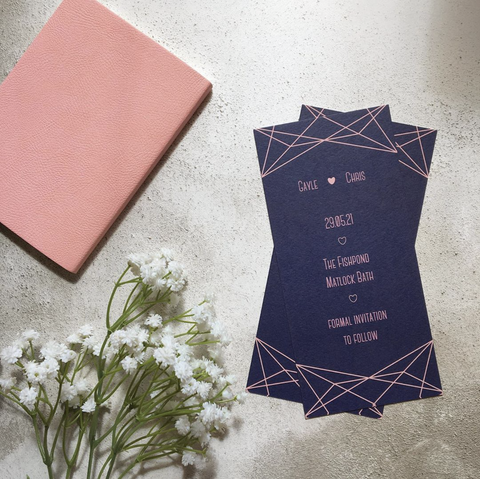 Blush and navy bookmark-style wedding invitation/save the date. The background colour is navy blue, and there is a geometric pattern on the top and bottom which is blush. The text is also blush.