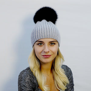 beanie hat ribbed handknitted in gray extra fine merino wool with an extra large black fox fur pompom