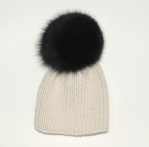 beanie hat ribbed handknitted in off-white extra fine merino wool with an extralarge black fox fur pompom