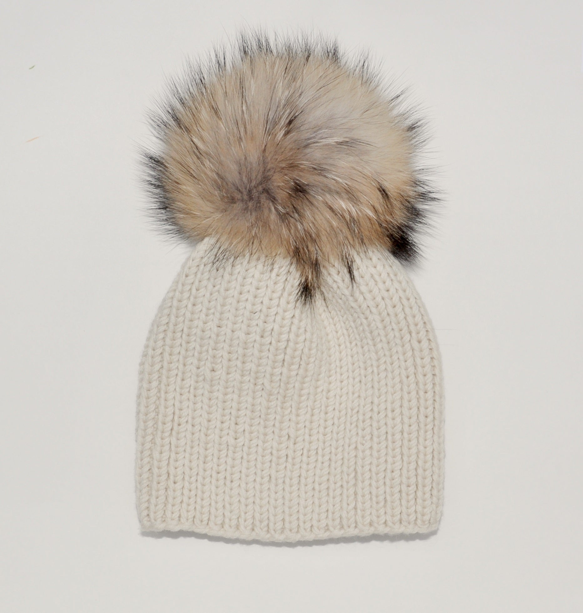 beanie hat ribbed handknitted in off-white extra fine merino wool with a large finn raccoon fur pompom matching
