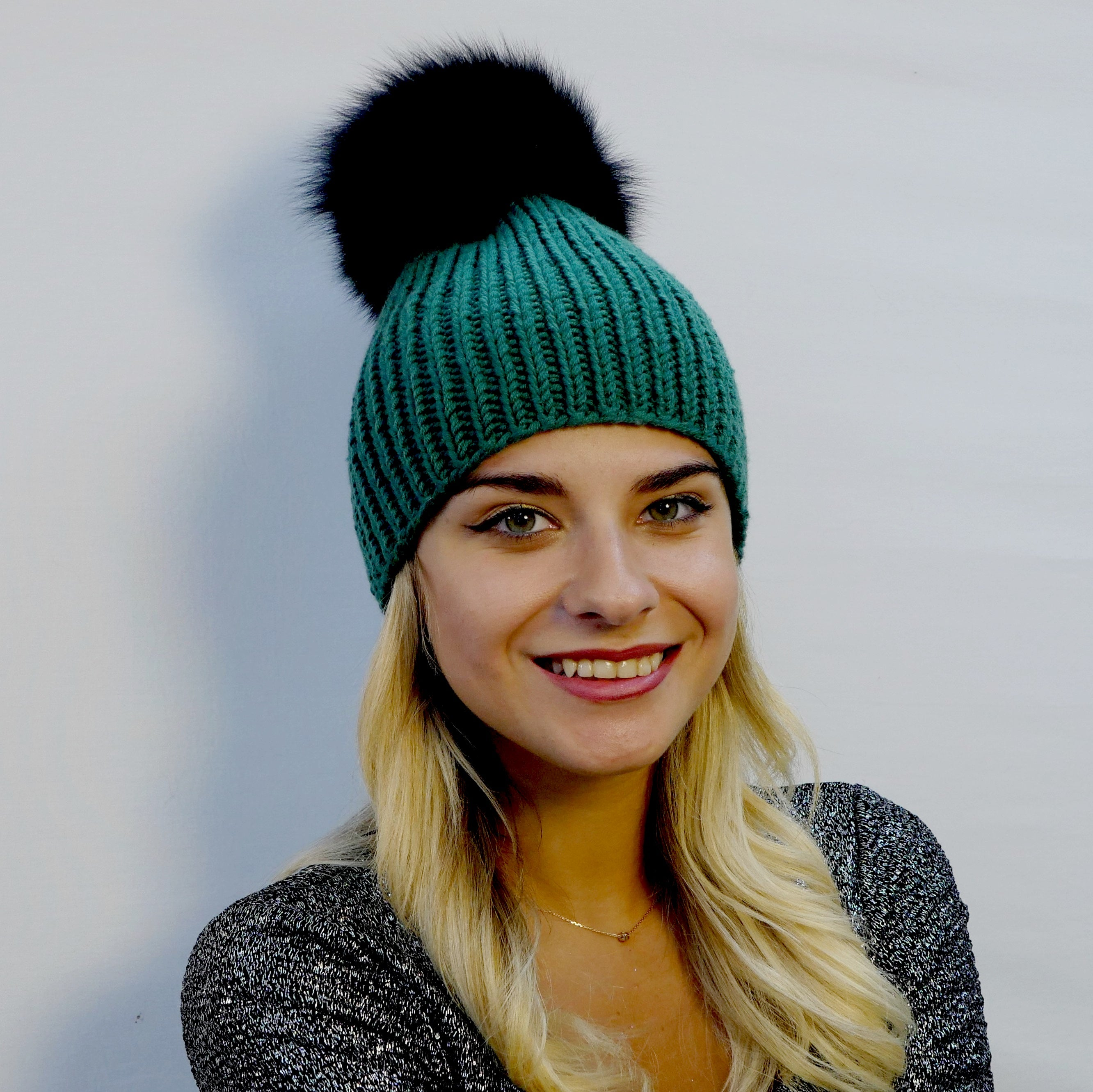 beanie hat ribbed handknitted in pine green extra fine merino wool with an extra large black fox fur pompom
