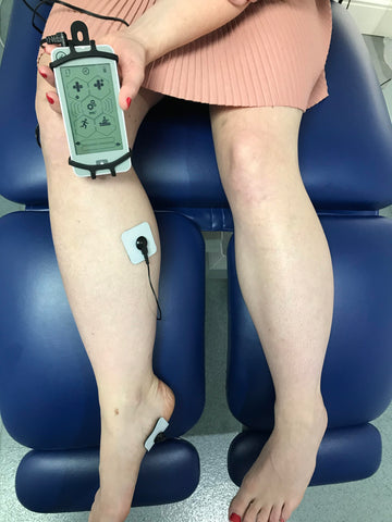 Lady in a Podiatrists office using the NuroKor mitouch device to treat her right foot and knee.