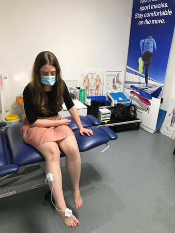 Lady in Podiatrists office using NuroKor mitouch device