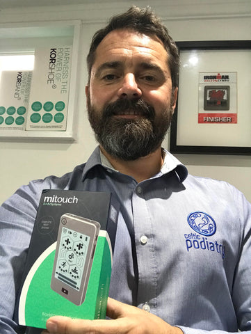 Jamie Tilly holding his NuroKor mitouch device.