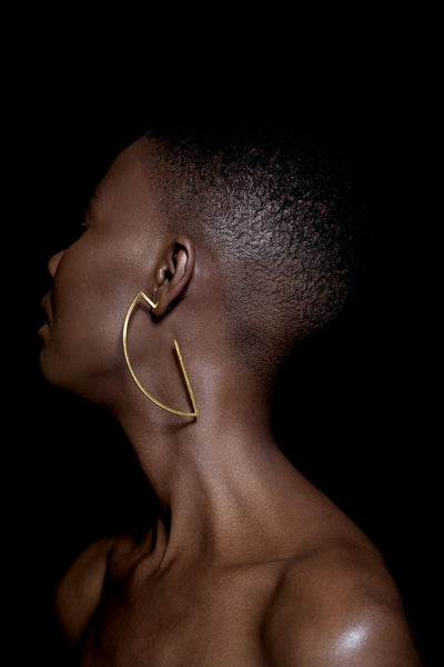 Black woman with a shaved head is wearing gold oversize geometric hoops earrings handcrafted by ROKUS London.