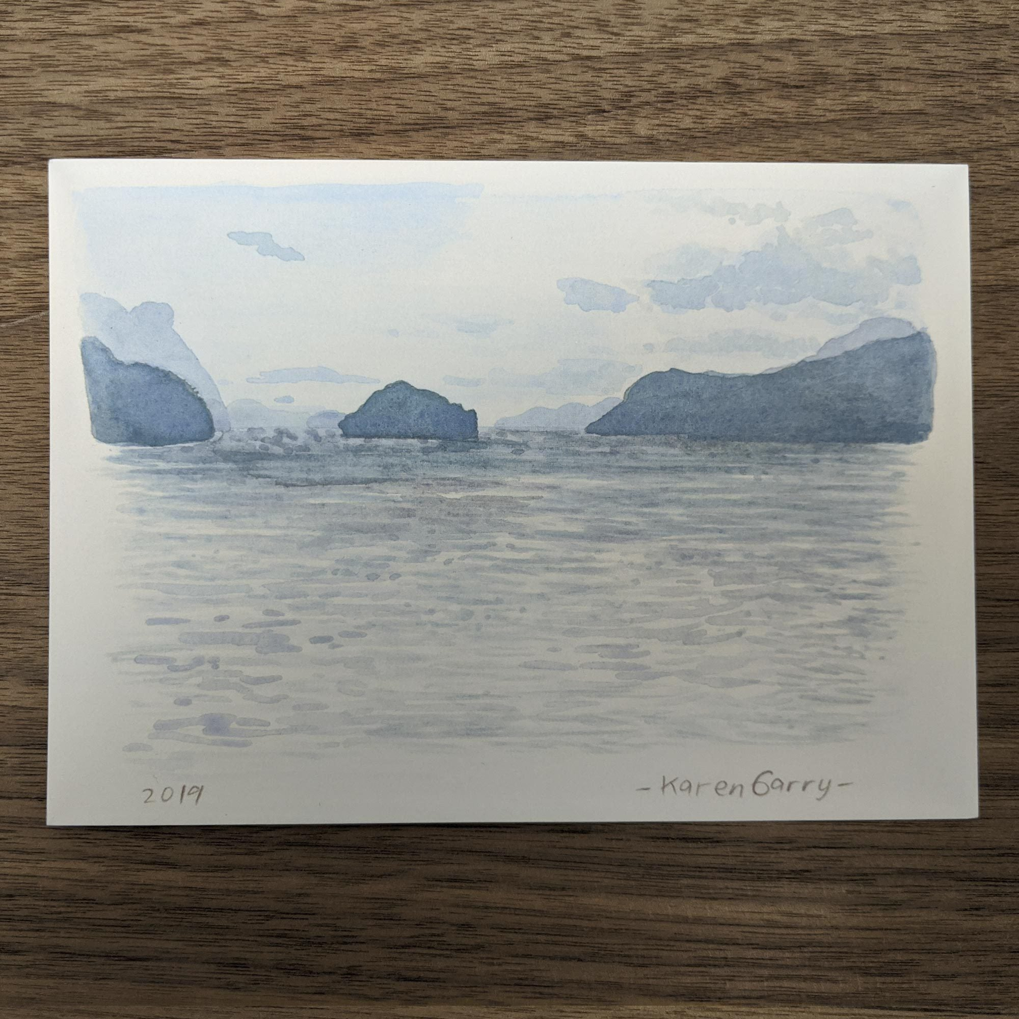 Hand painted postcard of the beach with islands on the horizon.