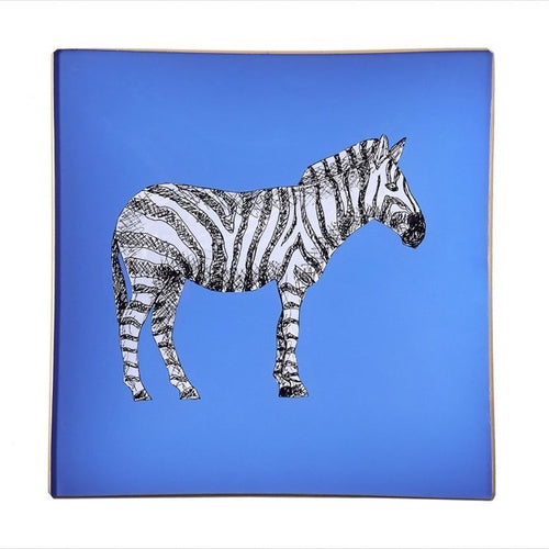 An artisanal, decorative glass valet tray with a zebra illustration on a cornflower blue background finished with an 18kt gold leaf edging