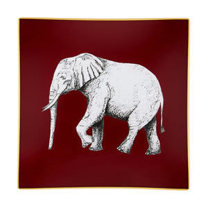 A decorative glass tray with an elephant illustration on a burgundy background finished with an 18kt gold leaf edging