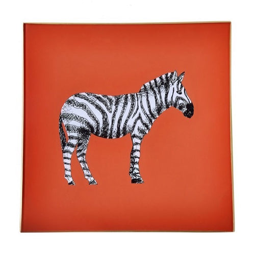 An artisanal, decorative glass valet tray with a zebra illustration on an orange background finished with an 18kt gold leaf edging