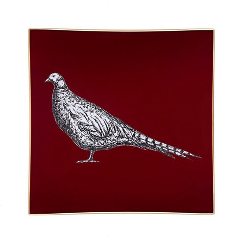 A decorative glass tray with a pheasant illustration on a burgundy background finished with an 18kt gold leaf edging