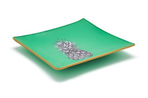 An artisanal, decorative glass valet tray with a pineapple illustration on a mint green background finished with an 18kt gold leaf edging