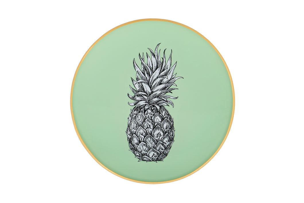 An artisanal, decorative glass round tray with a pineapple illustration on a pale sage green background finished with an 18kt gold leaf edging