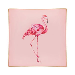 A decorative glass tray with a flamingo illustration on a blush pink background finished with an 18kt gold leaf edging