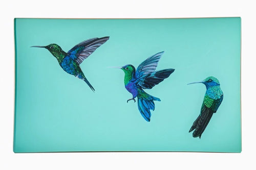 A decorative glass valet tray with three hummingbird illustrations on an aqua background and finished with an 18kt gold leaf edging