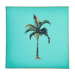 An artisanal, decorative glass valet tray with a palm tree illustration on a turquoise background finished with an 18kt gold leaf edging