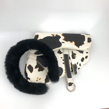Load image into Gallery viewer, cow print design atop the iconic saddle-shaped bag structure photo. Featuring a black fur headband