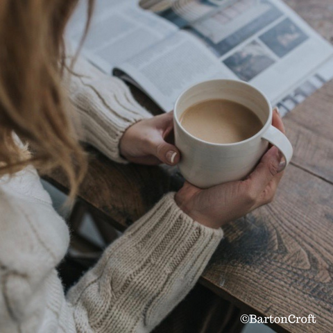 A woman in a cosy cable knit jumper reading the paper at a wooden table with her hands wrapped round a warm mug of tea