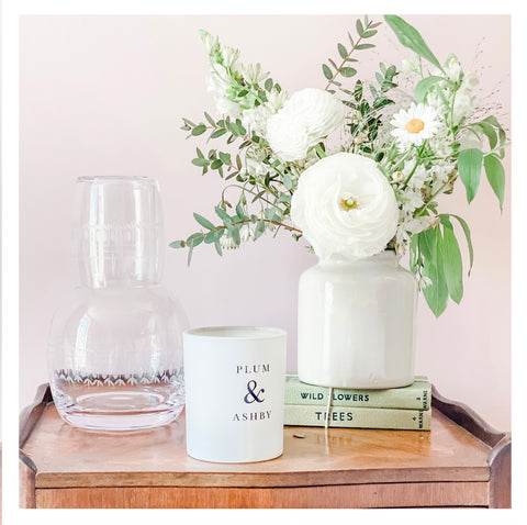 A bedside table with a candle, flowers and a carafe of water