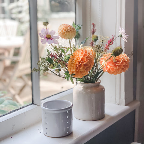 A vase full of Autumnal Dahlias and a handmade tealight holder on a cottage window