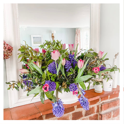 A display of flowers, tulips and hyacinths on a vase on a mantelpiece