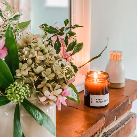 A lit candle on an old brick fireplace alongside a beautiful bunch of handpicked flowers